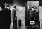 抽着雪茄,拿着小提琴箱,从帝国宾馆的电梯里面走出来。