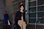 当地时间10月16日,结束工作的超模贝拉·哈迪德离开位于纽约的一间摄影棚。当天,贝拉身穿黑色开衫打卡其色条纹长裤,头顶毛线帽,心情大好的她还对镜微笑。