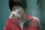 """近日,由陈可辛执导的电影《中国女排》再曝拍摄路透。照片中,饰演""""铁榔头""""郎平的巩俐,一身红色运动服,戴着眼镜,坐在板凳上,似在与周边的队员们开会。"""