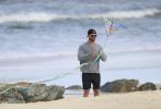 """近日,一组""""锤哥""""克里斯·海姆斯沃斯带孩子们在海滩放风筝的照片曝光。照片中,锤哥身穿灰色卫衣搭黑色短裤。墨镜遮面,反戴棒球帽,帅气十足。他和孩子们一起漫步在海边放风筝,不时还将儿子亲亲抱抱举高高,脸上挂着温柔的笑容,父爱满溢。"""
