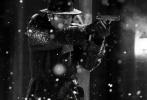 """5月12日,于和伟分享一组自己在电影《悬崖之上》中所饰角色""""周乙""""的黑白剧照。照片中,一袭黑衣亮相的他在雪中持枪作战,身手矫健,神情凝重。"""